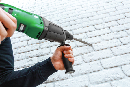 worn: Use hammer drill to drill the wall Stock Photo