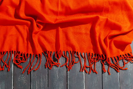 Red scarf over black wood table background