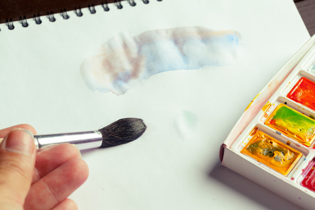 easel: Set of watercolor paints and paintbrushes for painting