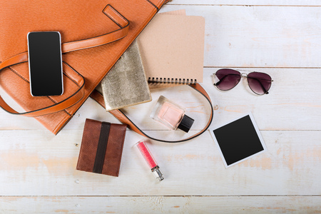 View on women bag stuff on wooden background Stock Photo