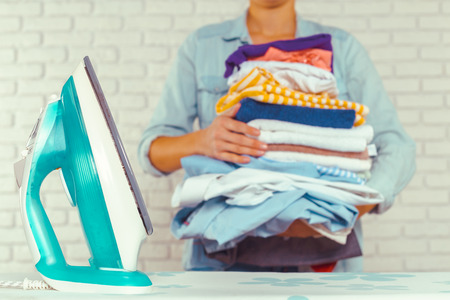 messy clothes: Housewife bringing a huge pile of laundry on the ironing board Stock Photo