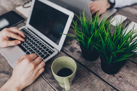 ビジネスマンは、自分のコンピューターに取り組んでいます。頂上からの眺め