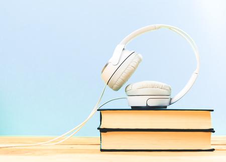 Konzept des Hörbuchs. Bücher auf dem Tisch mit Kopfhörer auf sie auszuüben Standard-Bild - 76923463