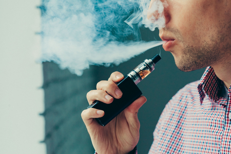 Close up on a man exhaling vapor from an electronic cigarette