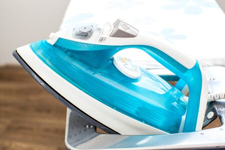 domestic task: Iron on ironing board on light home interior background Stock Photo
