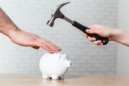 A hand holding a hammer which is raised above a white piggy bank 版權商用圖片 - 77064009
