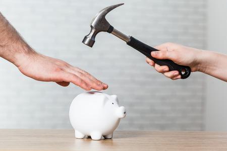 Een hand die een hamer houdt die boven een witte spaarvarken wordt opgewekt Stockfoto