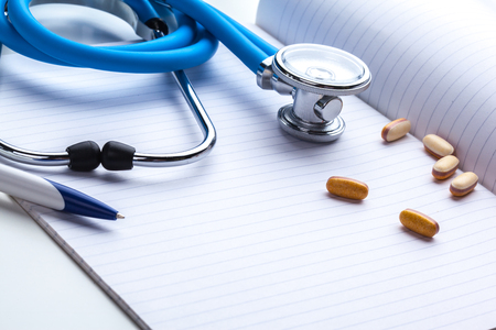 pharmacologist: Empty prescription  lying on table with stethoscope