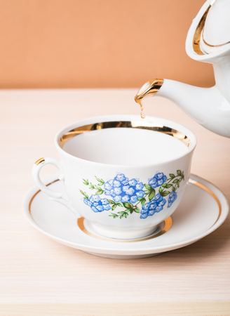 Old-style porcelain kettle pouring tea from jug to cup of tea Stock Photo