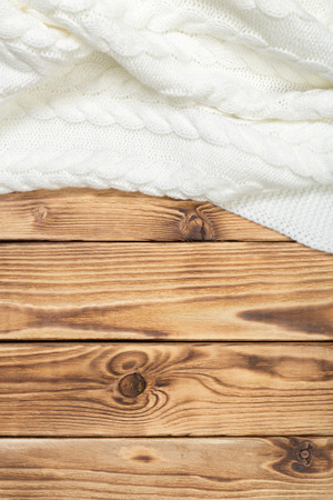 wooden surface: cozy knitted blanket on wooden boards