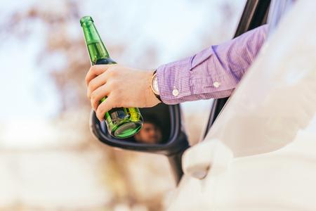 violación: hombre bebiendo alcohol mientras maneja el auto