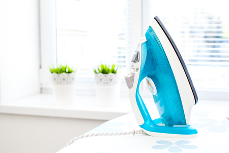 shirt hanger: Iron on ironing board on light home interior background Stock Photo
