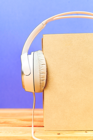 them: Concept of audiobook. Books on the table with headphones put on them
