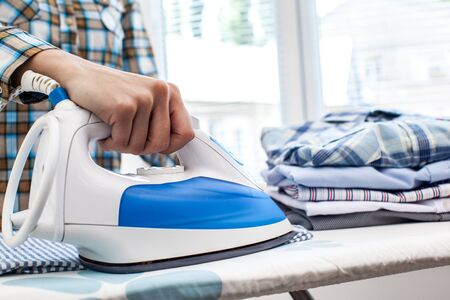 Closeup of woman ironing clothes on ironing board Stock Photo