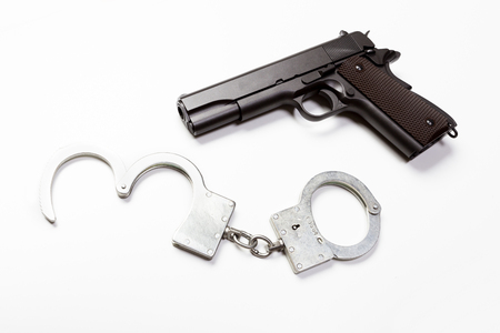 arrested criminal: gun and handcuffs on white background Stock Photo