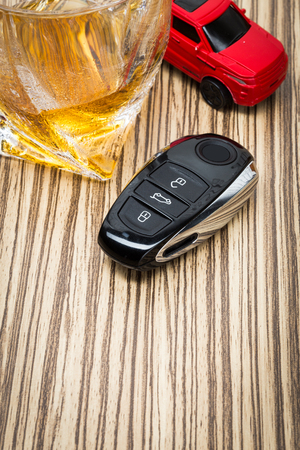 intoxicate: toy car and glass of whiskey metaphor crash accident isolated on white Stock Photo
