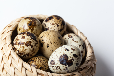 Fresh quail eggs at wooden plate closeup