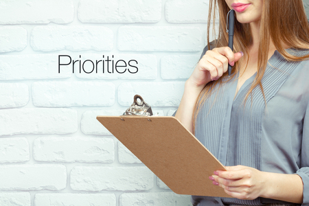businesswoman with clipboard and pen making notes and standing near priorities text