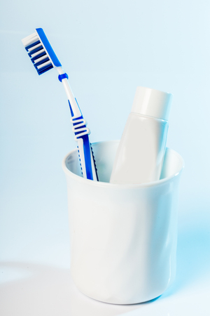 gum paste: Toothbrushes in glass on table on light background