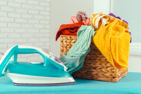 Iron on ironing board on light home interior background Stock Photo
