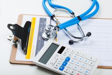 Costi sanitari. Stetoscopio e calcolatrice Archivio Fotografico - 77846783
