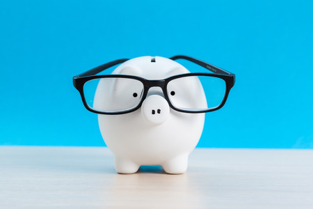 Piggy bank with glasses on blue background