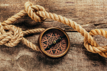 fixed line: ship ropes and compass on wooden background Stock Photo