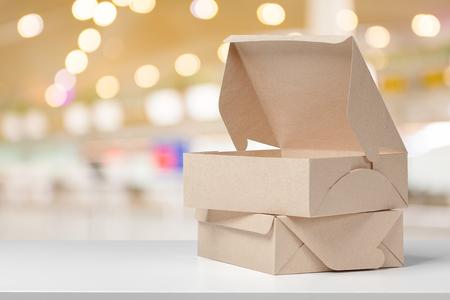 Caja de cartón en el escritorio blanco Foto de archivo - 77845343