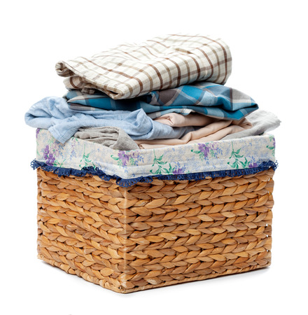 messy clothes: Clothes in a laundry wooden basket isolated on white background Stock Photo