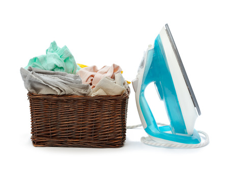 Electric iron and pile of clothes. Stock Photo