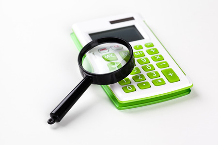 multiplicacion: Calculator with a magnifying glass on a white background Foto de archivo