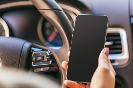 body parts cell phone: close up of woman using smartphone while driving car