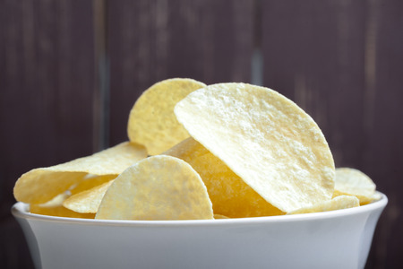 Potato chips in bowl on a table Stock Photo