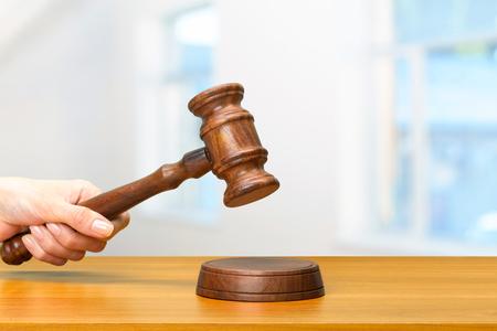 iemands hand met houten wet hamer