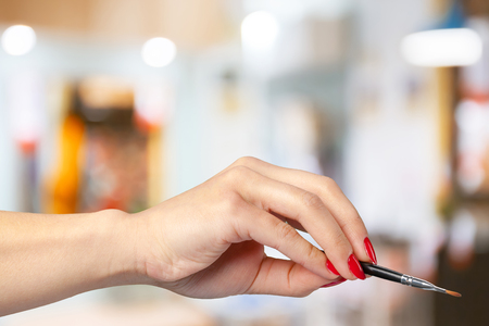 grooming product: female hand holding a professional makeup brush