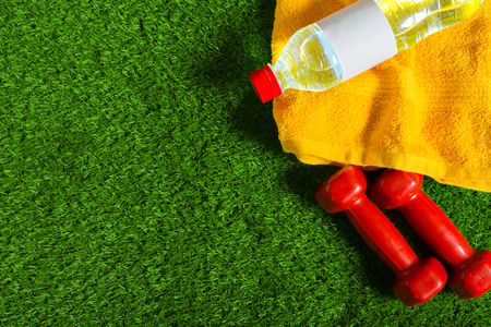 greengrass: water bottle, red dumbells and towel on green grass background