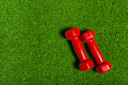 red dumbbell on green grass Stock Photo