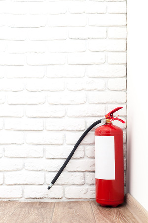 to mend: Fire extinguisher near white wall, ready for use