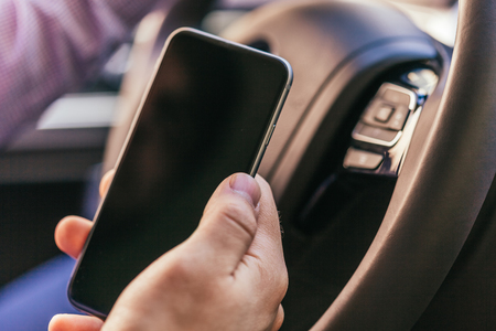 close up of young man hand with smartphone driving car