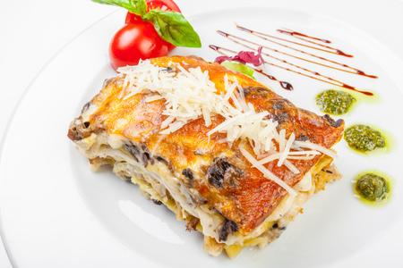 Gedeelte van smakelijke lasagne, geïsoleerd op wit