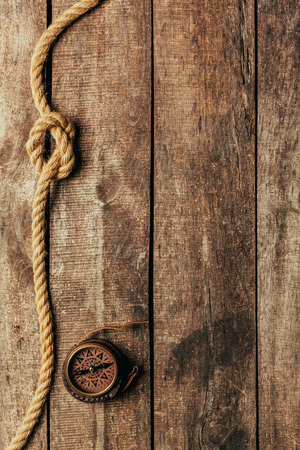 twist: ship ropes and compass on wooden background Stock Photo