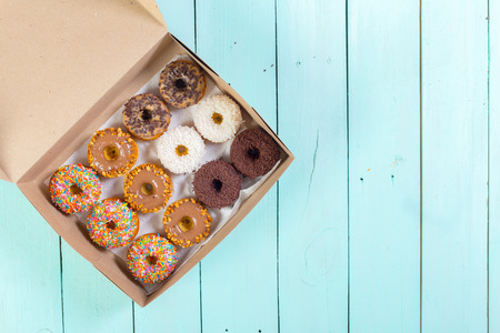 Donuts in box on wooden table. Top view
