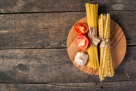 traditional culture: Several types of dry pasta with tomatoes. On wooden background.