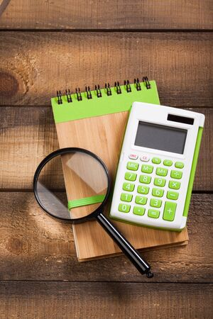 sheet: notebook on a brown wooden background with a calculator and magnifying glass