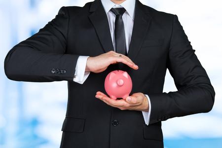 Unrecognizable businessman holding pink piggy bank