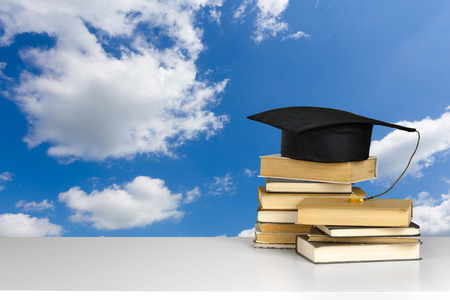 heap: books and mortarboard on wooden table