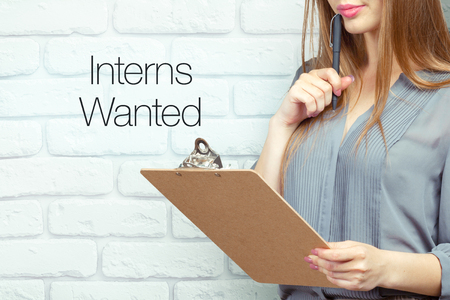 businesswoman with clipboard and pen making notes and standing near text: Interns wanted