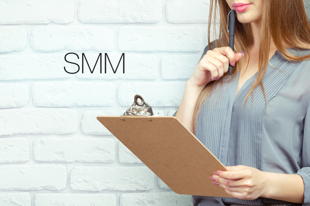 businesswoman with clipboard and pen making notes and standing near text: SMM Stock Photo