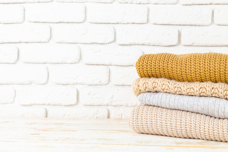 Stack of white cozy knitted sweaters Stock Photo - 86357931