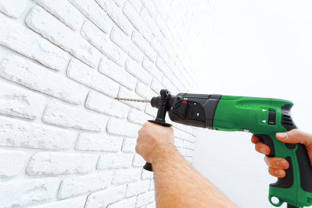Use hammer drill to drill the wall Stock Photo